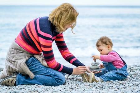 Mother and her baby playing with pebbles on the beach Stock Photo
