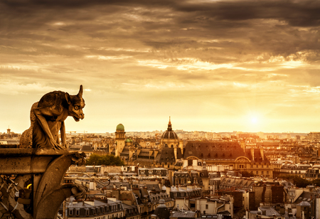 gargouille: Chimera (gargoyle) of the Cathedral of Notre Dame de Paris overlooking Paris at sunset, France Banque d'images