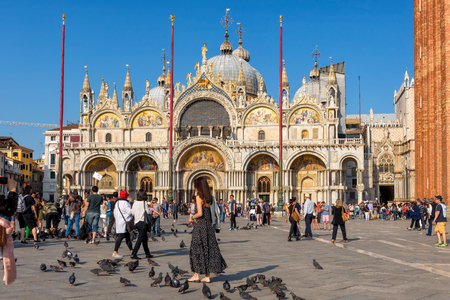 Venice, Italy - May 18, 2017: Tourists are walking around the Basilica di San Marco on the Piazza San Marco (St. Marks Square). This is the main square of Venice.