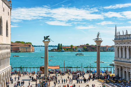 Venice, Italy - May 21, 2017: Piazza San Marco, or St Mark`s Square, in Venice, Italy. Embankment with famous columns. The lagoon of Venice.