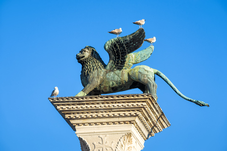 winged lion: The famous ancient winged lion sculpture in the Piazza San Marco on the blue sky background in Venice, Italy. The lion is a symbol of Venice.