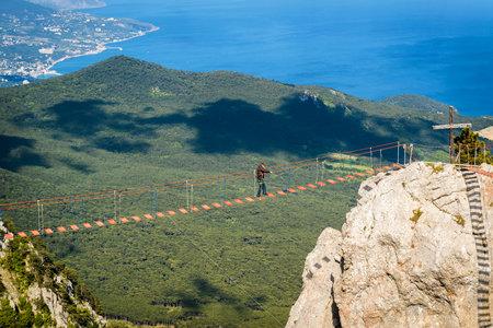 steep: CRIMEA, RUSSIA - MAY 19, 2016: Tourist walking on rope bridge on the Mount Ai-Petri. Ai-Petri is one of the highest mountains in Crimea and tourist attraction.