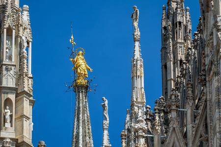 De Madonnina boven op de kathedraal van Milaan in Milaan, Italië. Dit standbeeld werd opgericht in 1762 op een hoogte van 108,5 m. Milan Duomo is de grootste kerk in Italië en de vijfde grootste ter wereld. Stockfoto