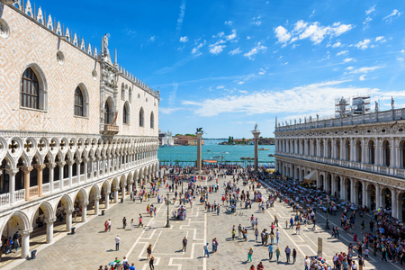 Venice, Italy - May 21, 2017: Tourists walk around the Piazza San Marco, or St Marks Square. The famous Doges Palace on the left. This is the main square of Venice.