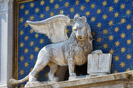 The statue of the winged lion on the Cklock Tower (Torre dellOrologio) in the St. Marks Square in Venice, Italy. The winged lion is a symbol of Venice. Stock Photo