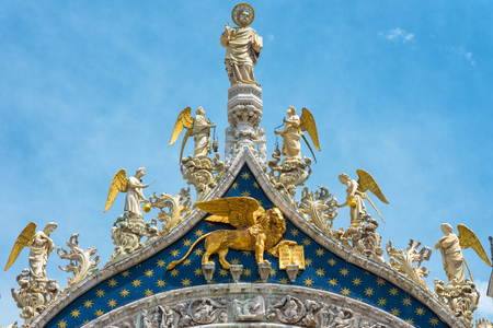 winged lion: St. Mark`s Apostle, angels and the gilded lion on the top of the Basilica di San Marco facade (Saint Mark`s Basilica) in Venice, Italy. The winged lion is a symbol of Venice.