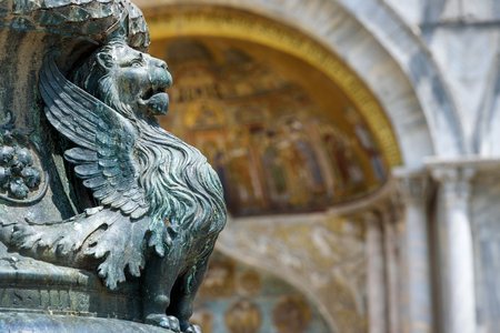 Detail of the architecture of the Saint Mark`s Square, winged lion, in Venice, Italy. Basilica di San Marco in the background. The winged lion is a symbol of Venice. Stock Photo