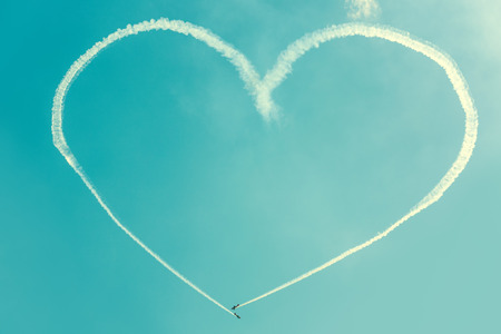 A heart in the blue sky from two skywriting small planes at an air show Stock Photo