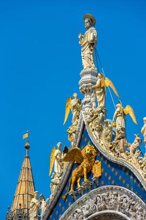 Top of the facade of the Basilica di San Marco (Saint Mark`s Basilica) in Venice, Italy. Statue of St. Mark the Apostle - the patron saint of Venice.