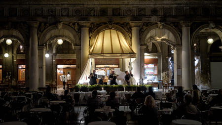 Venice, Italy - May 19, 2017: Musical band plays for tourists in the outdoor restauranton on the Piazza San Marco (St Mark`s Square) at night. This is the main square of Venice.