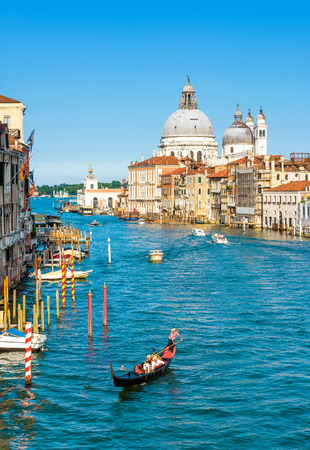 Gondola and water taxis are sailing along the Grand Canal in Venice, Italy. Grand Canal is one of the major water-traffic corridors in Venice. Santa Maria della Salute in the distance. Editorial