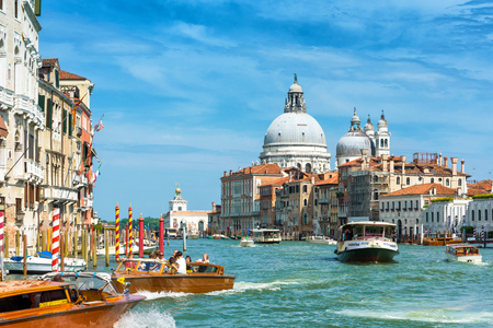 Venice, Italy - May 19, 2017: Water taxis with tourists are sailing along the Grand Canal. Motor boats are the main transport in Venice. Basilica Santa Maria della Salute in the distance.