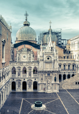 Courtyard of Doge`s Palace, or Palazzo Ducale, in Venice, Italy. Doge`s Palace is one of the main tourist destination in Venice. Domes of Saint Mark`s Basilica in the background.