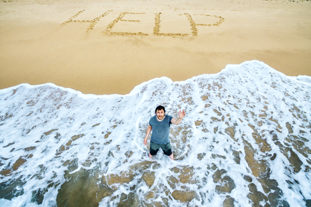 A man is calling for help on the beach of an uninhabited island. Inscription HELP on the sand.