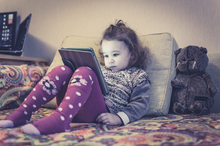 Little girl sits on a couch and uses a digital tablet. Two-year child looks electronic device at home. Banque d'images