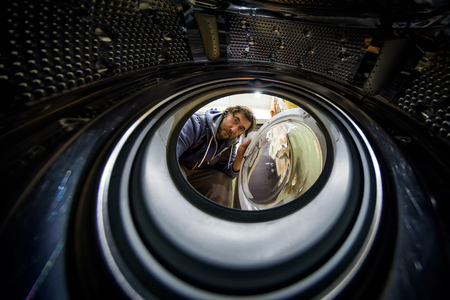The man looks inside. View from the inside of washing machine.