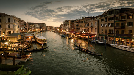 Grand Canal with gondolas at night in Venice, Italy. Grand Canal is one of the major water-traffic corridors in Venice.
