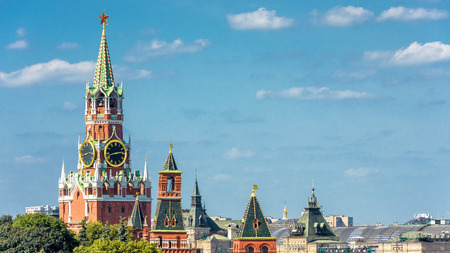 The Moscow Kremlin with the Spasskaya tower on the blue sky background, Russia. The Moscow Kremlin is the residence of the Russian president and the main tourist attraction of Moscow.