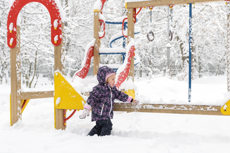 Little child plays on the snowy playground in winter. Happy baby girl walks during snowfall. Banque d'images