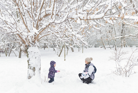 Little child with mother walk in a snowy park in the winter. Baby girl plays in snow. Family walks during snowfall. Banque d'images