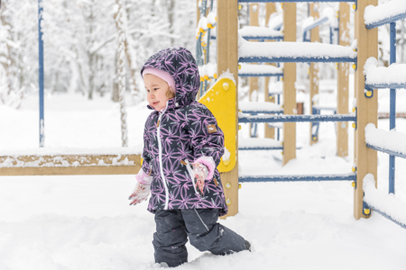 Little child plays on the snowy playground in winter. Unhappy baby girl goes to her parents during snowfall. Banque d'images