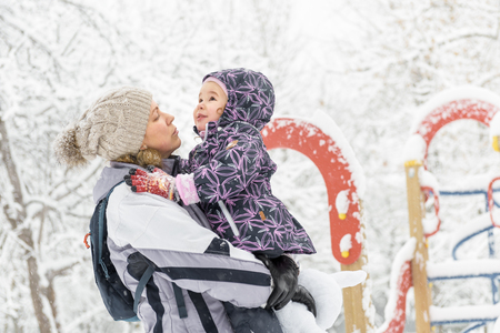 Cheerful little child plays with mother in a snowy park in winter. Happy family walks during snowfall. Cute baby girl sits on the mothers hands.