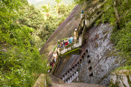 Mulkirigala, Sri Lanka - November 4, 2017: Tourists descend the stairs from the ancient Buddhist rock temple. Ancient steps carved into the rock, in the foreground Éditoriale