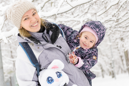 Cute cheerful little child plays with mother in a snowy park in winter. Happy family walks during snowfall. Banque d'images
