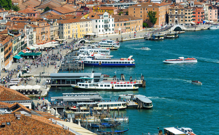 Main embankment in Venice, Italy. Seafront with piers for tourist boats in Venetian lagoon.