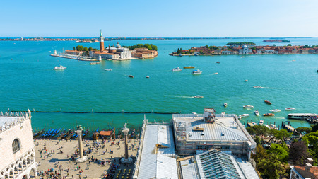 Aerial panoramic view of Venice, Italy. Piazza San Marco, or St Mark`s Square, and seafront with gondolas. Island of San Giorgio Maggiore in the lagoon of Venice in the distance.