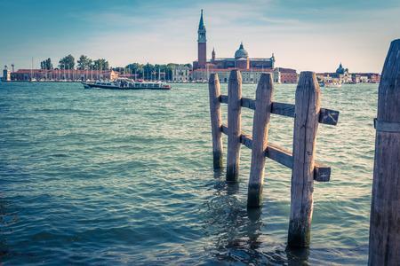 Venice, Italy. Old berth. View of Venetian lagoon with tourist boat and San Giorgio Maggiore island from Saint Mark`s Square. Motor boats are the main transport in Venice.