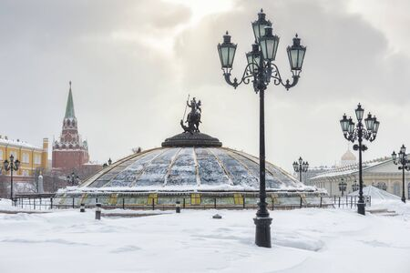 Manezhnaya Square in central Moscow in the winter. Glass cupola crowned by a statue of Saint George, holy patron of Moscow. Kremlin in the background. Banque d'images