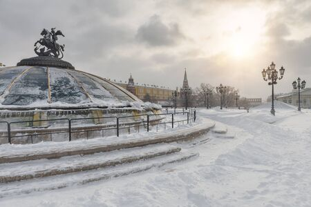 Manezhnaya Square in the winter, Moscow, Russia. Panoramic view of central Moscow during snowfall. Glass cupola crowned by a statue of Saint George, holy patron of Moscow, in the foreground.