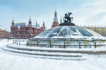 Manezhnaya Square in the winter in Moscow, Russia. View of central Moscow during snowfall. Glass cupola crowned by a statue of Saint George, holy patron of Moscow, in the foreground.