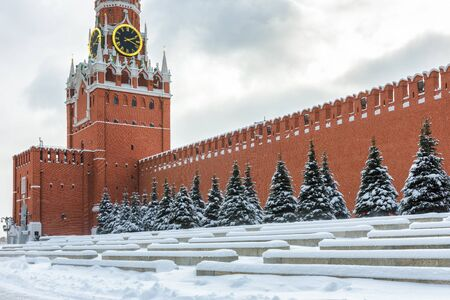 Moscow Kremlin with Spasskaya Tower on the Red Square during snowfall in winter, Moscow, Russia. The Red Square is the main tourist attraction of Moscow.