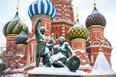 St. Basil`s Cathedral and monument to Minin and Pozharsky on the Red Square during snowfall in winter, Moscow, Russia. The Red Square is the main tourist attraction of Moscow.