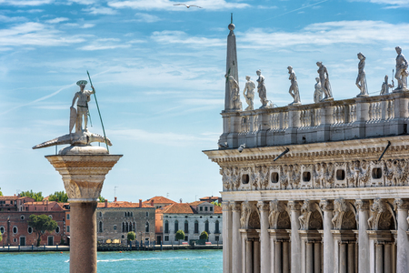 San Marco Square in Venice, Italy. Ancient statue of St Theodore and Library of St Marks. San Marco (Saint Mark`s Square) is the main travel attractions of Venice. Historical architecture and landscape of Venice.
