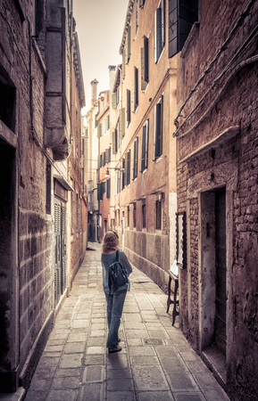 Girl tourist is on a narrow street in Venice, Italy.