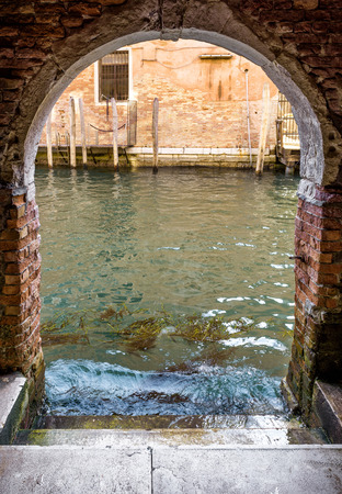 Entrance to the residential area from water canal in Venice, Italy. Exit to the street from the courtyard. Water trip in Venice. Historical architecture and canals of Venice. Unusual streets and buildings of Venice.