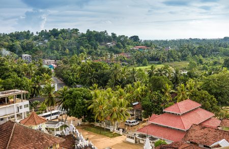 Landscape in Dickwella town, Sri Lanka. Wewurukannala Vihara Buddhist temple in the foreground. Panoramic view of tropical forest in Sri Lanka. Buddhist travel destinations in Sri Lanka.