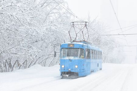 Tram goes along the street during snowstorm at winter in Moscow, Russia. Cold and snowfall in Moscow. Icy tram in snowy Moscow. Traditional view of Moscow street at winter. Russian blizzard.