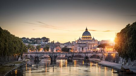 Rome at sunset Italy. Sant`Angelo bridge and St Peters Basilica. Rome landmark. Saint Peters Basilica (San Pietro) is one of main travel attractions of Rome. Scenic view of night Rome and Vatican. Banque d'images