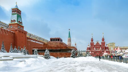 Moscow, Russia - February 5, 2018: Moscow Kremlin with Lenin's Mausoleum on Red Square in winter during snowfall. Red Square is the main tourist attraction of Moscow. Travel across winter Moscow.