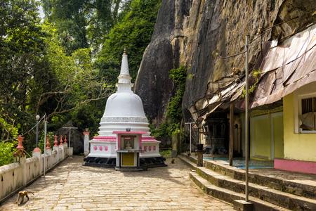 Buddhist old temple of Mulkirigala in the sunlight in Sri Lanka. Mulkirigala Raja Maha Vihara is an ancient Buddhist rock and cave temple complex. It is one of main travel attractions of Sri Lanka.  Stock Photo