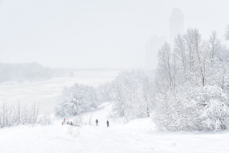 Winter landscape, Moscow, Russia. People walk in the park near Moskva River during snowfall. Winter Moscow outdoor background. Scenic view of a snowy beach in Moscow. Cold and snowstorm in Moscow.