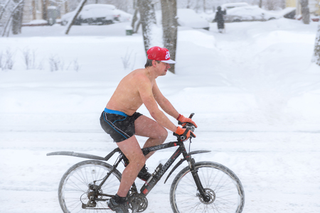 Moscow, Russia - February 4, 2018: A naked man rides a bike along the street during snowfall in winter. An eccentric rides a bicycle. Winter sport outdoor in Moscow. Russian winter traditions.