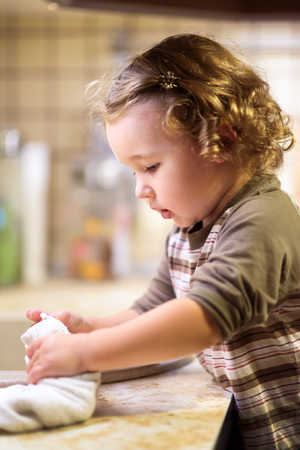 Ð¡ute two-year-old girl washes dishes in the kitchen. Baby helps the parents. Nice little child learns the household. Toddler wipes his hands with a towel. Adorable baby does house cleaning.