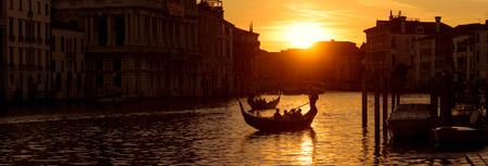 Panoramic view of Venice at sunset, Italy. Horizontal banner of Venice for website header. Gondolas with tourists sail along the Grand Canal in Venice. Romantic water trip in Venice at dusk.