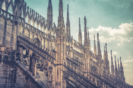 Amazing view of the Milan Cathedral roof (Duomo di Milano) in Milan, Italy. Beautiful luxurious top of Milan Cathedral with rows of Gothic pinnacles on the sky background. It is a main landmark of Milan. 免版税图像