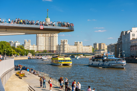 Moscow - June 16, 2018: Tourist ships sail on Moskva River past the Floating bridge in Zaryadye Park, Russia. Zaryadye is one of the main landmarks of Moscow. People relax in Moscow centre in summer. Editorial